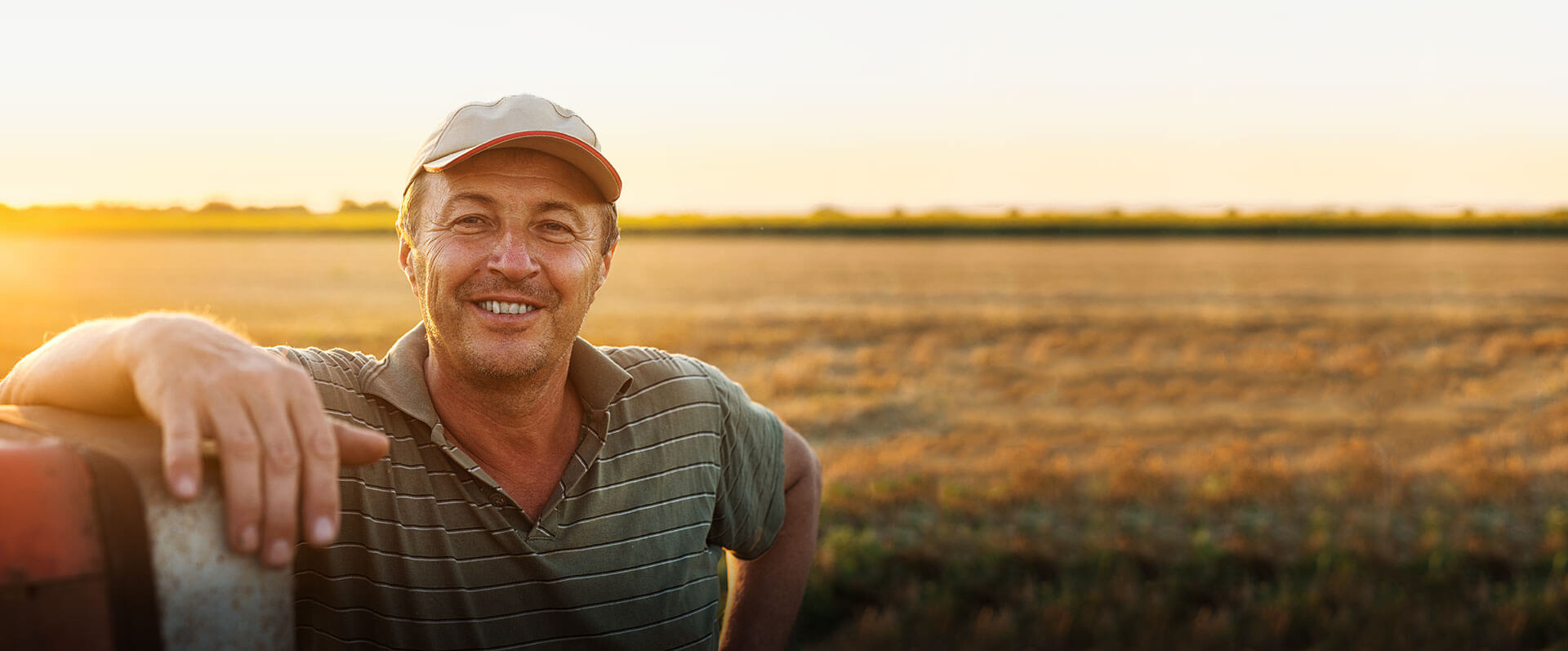 Image of Farmer Leaning on a truck in a field at sunset